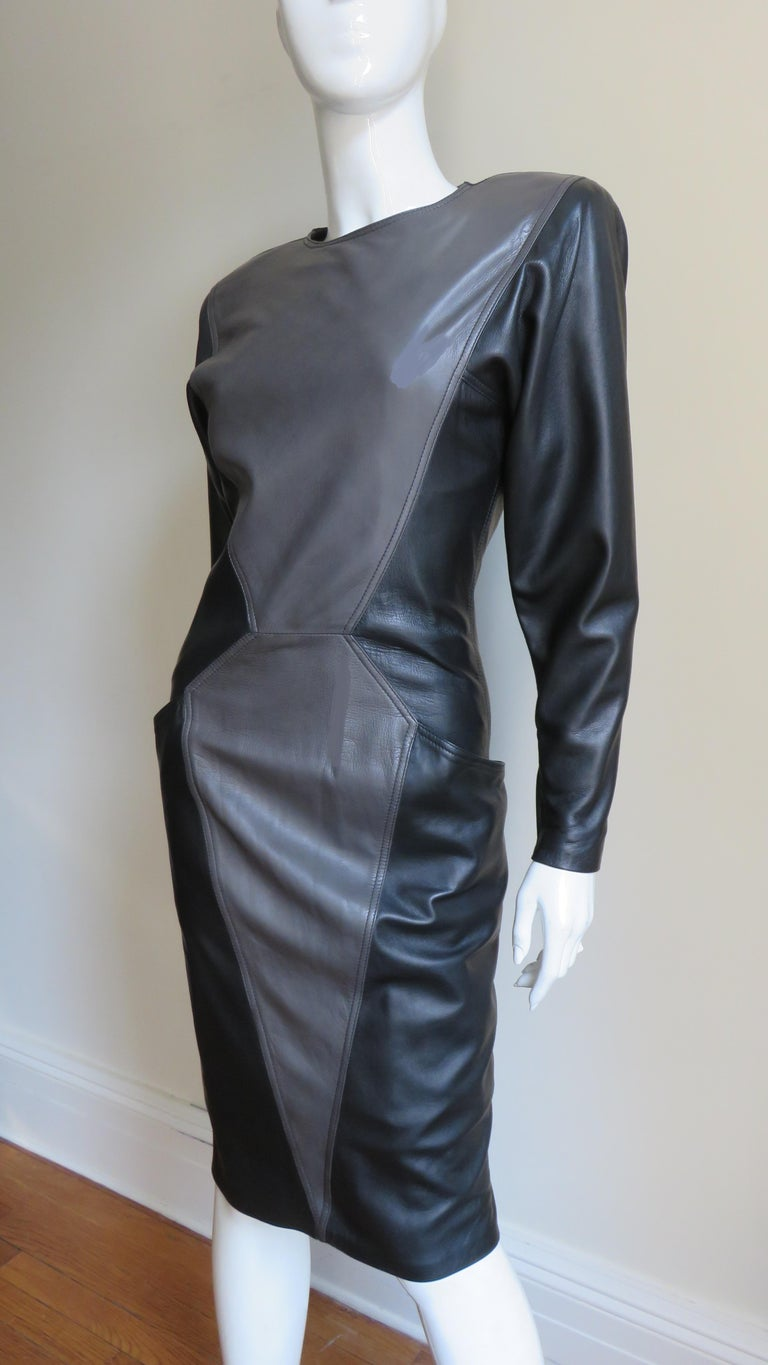 A fabulous soft, supple leather dress by Emanuel Ungaro in black and grey.  It has a crew neckline, long sleeves with zipper cuffs and shoulder pads.  The dress is black with a grey center front angled panel on the bodice and skirt flatteringly