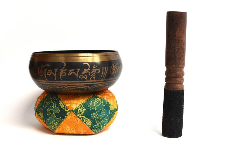 A bronze Tibetan singing bowl with embossed interior of 5 Buddhas in stellate form surrounded by a band of peacock feathers. Tibetan Sanskrit prayers decorate the exterior. Bowl is of perfect proportion, smooth and solid to hold, and creates a