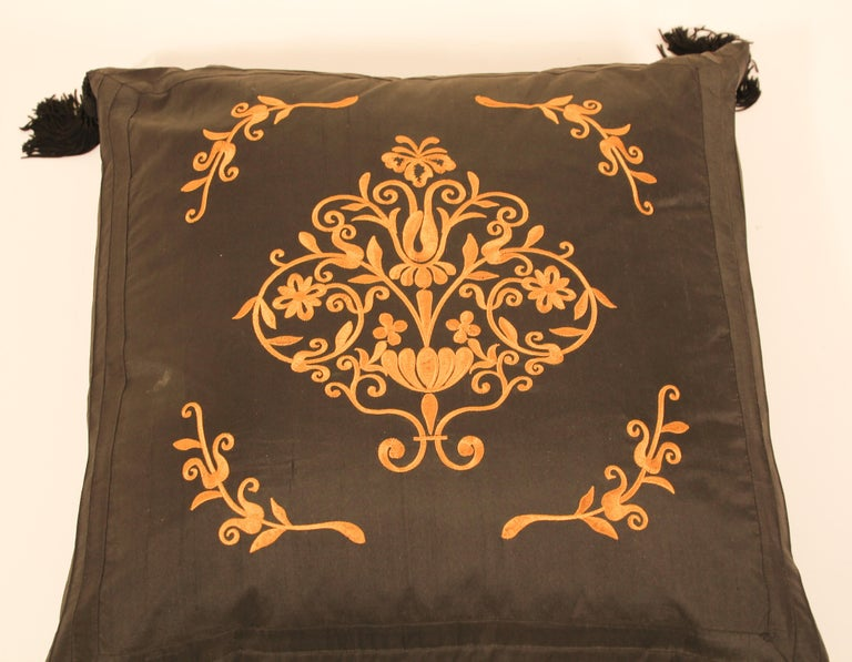 Black silk decorative accent pillow with tassels.