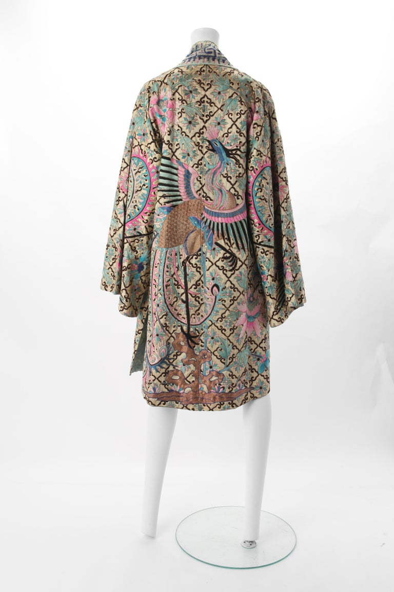 Embroidered Chinese Export Robe, Early 20th Century. Cream silk satin robe with all over embroidery in shades of blue, pink, black & metallic gold. Dominant motif of peacock and flowers against the diamond grid. Fits US Size 0 to 6.