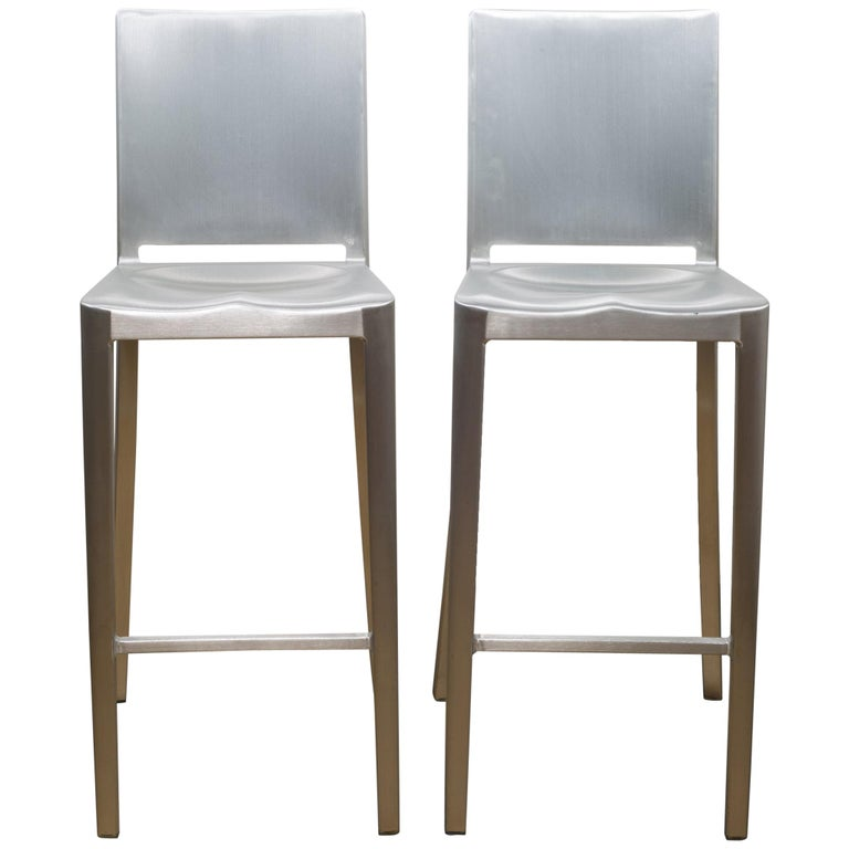 About  Two have sold.   This is an original set of two brushed aluminum Emeco Hudson counter stools designed by Philippe Starck. The stools have retained their original finish and have the appropriate patina. Each stool has some blemishes. Two are