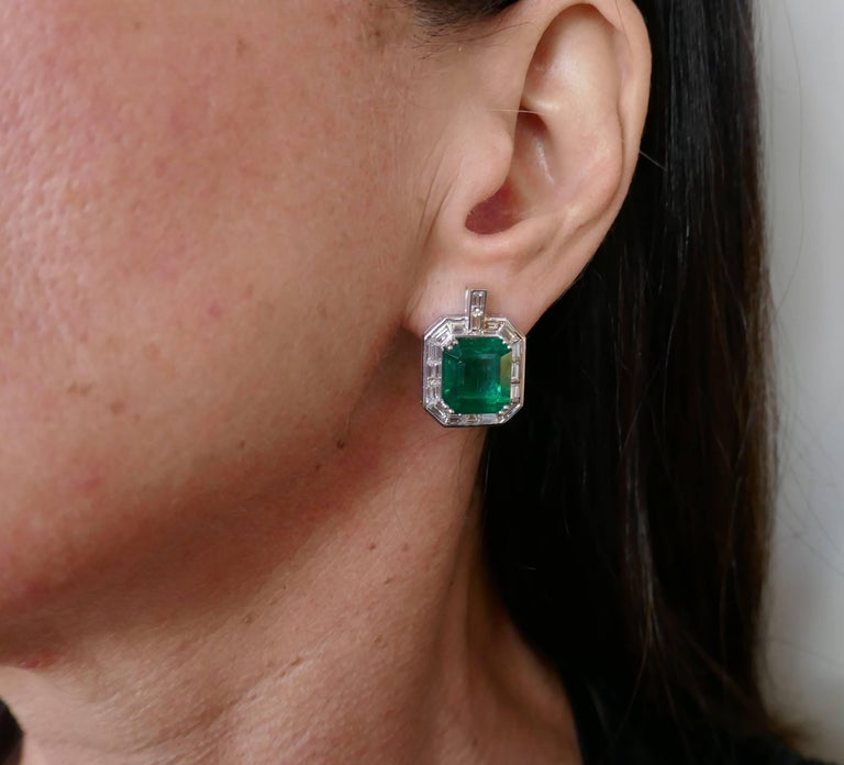 A pair of magnificent earrings featuring two Zambian emeralds. Classy, timeless and wearable, the earrings are a great addition to your jewelry collection.   The emeralds are framed with a row of sleek baguette cut diamonds and set in 18 karat white