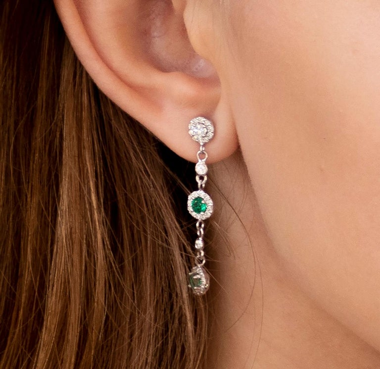 Fourteen karat white gold 1..75 inch drop earrings  Diamond weighing 1.30 carat Emeralds weighing 0.65 carat  New Earrings Handmade in USA The 14 karat gold earrings are hanging off a post with push backs Our design team select gemstones for their