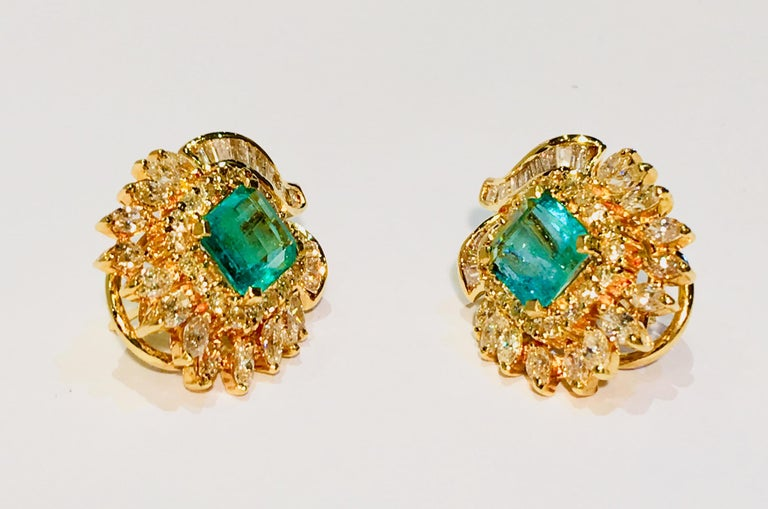 Contemporary, floral motif earrings feature large, prong set, emerald cut emeralds surrounded by prong set, round brilliant and marquise cut diamonds, and channel set, baguette cut diamonds in 18 karat yellow gold with posts and lever backs.  2