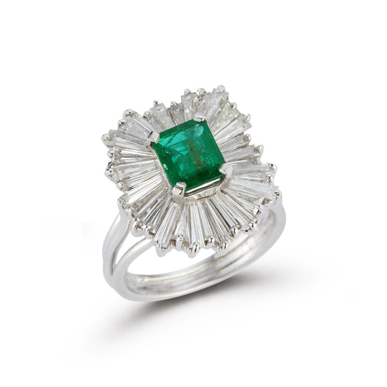Emerald and Diamond Ballerina Cocktail Ring  Platinum Ring with Center Emerald approximately 1.30 Carats Surrounded by an Array of Baguette Cut Diamonds approximately 2.54 Carats  Ring Size 5.5  Resizable Free of Charge