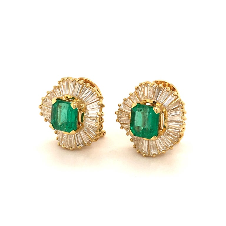 This sparkling pair of earclips in 18 karat yellow gold feature two octagonal-cut emeralds of approximately 2.16 carats and 2.23 carats resepctively. The lively coloured emeralds are haloed by 56 tapered-cut diamonds of G/H colour and vs clarity,