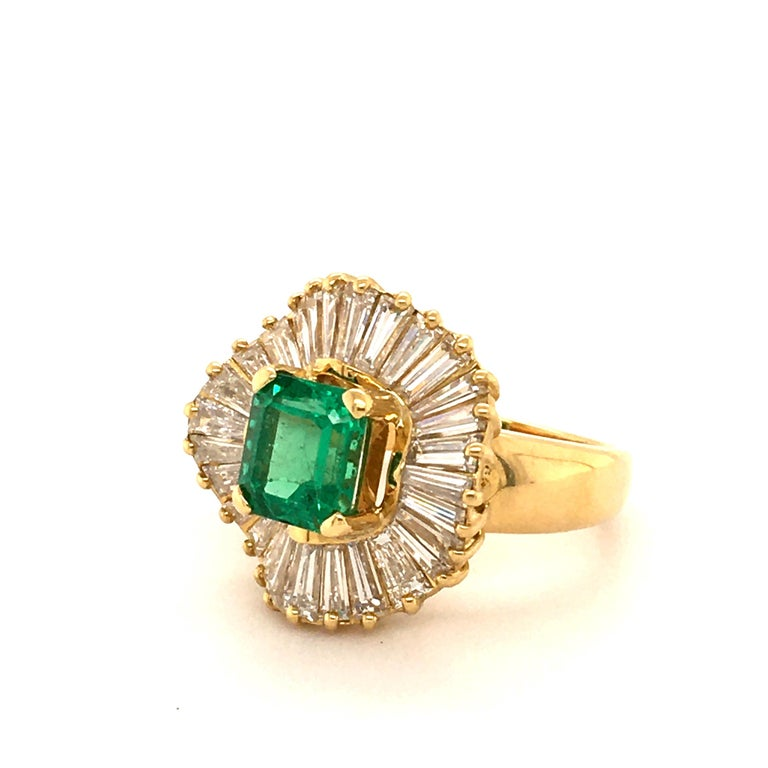 This beautiful ring in 18 karat yellow gold features a lively green emerald of approximately 2.10 carats. The octagonal cut emerald is haloed by 28 tapered-cut diamonds of G/H colour and vs clarity, total weight approximately 3.50 carats.  Ring