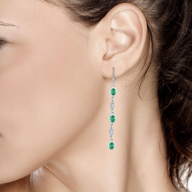 14 karat white gold hoop two inch long drop earrings  Diamond weighing 0.65 carat Emeralds weighing 17.5 carat  New Earrings Handmade in USA Our design team select gemstones for their quality, aesthetic beauty and sale value of the featured