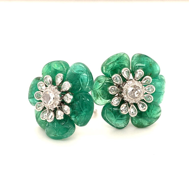 At a closer look, these charming emerald earclips reveal substantial carat weight!  Shaped as softly curved flower petals, the 12 fancy shaped and engraved emeralds have a total weight of approximately 42.00 carats. They are accented by 24 rose cut