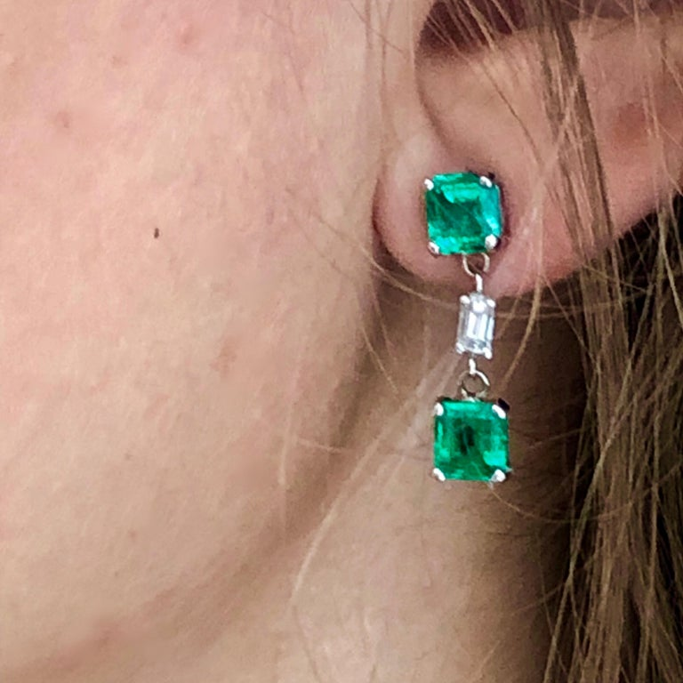 Fourteen karat white gold diamond and emerald drop earrings  Earrings are one inch long Two emerald cut diamond weighing 0.30 carat Four emerald cut emeralds weighing 3.35 carat  Diamond quality G VS Emerald quality bright and vivid green New