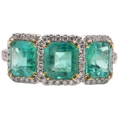 Emerald and Diamond Halo Trilogy Ring in 18 Carat White Gold