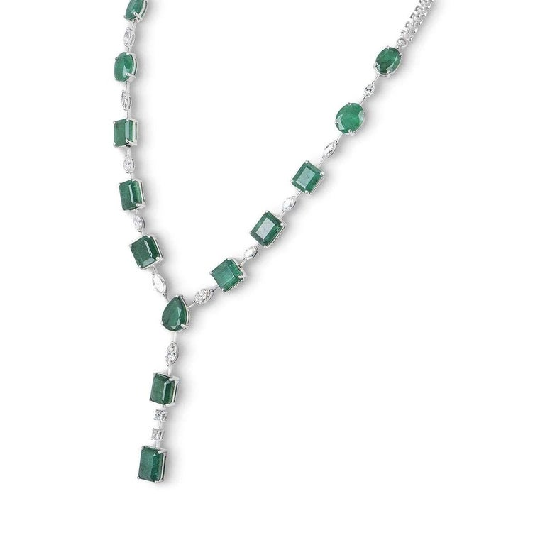 An 18k white gold necklace and earring jewellery suite. The necklace features 13 emeralds in a range of cuts, 11 marquise cut diamonds and 2 princess cut diamonds. The earrings are made up of an oval cut diamond, followed by 2 princess cut diamonds,