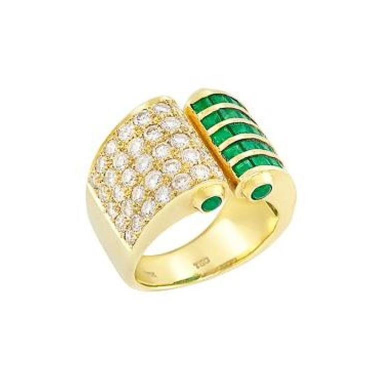 An extremely lively and unique design of a slightly open ring accented with emeralds and diamonds in 18K Yellow Gold. The ring consists of 35 round diamonds (appx. 1.20 cts.), square-cut emeralds, and 4 round cabochon emeralds on the sides.