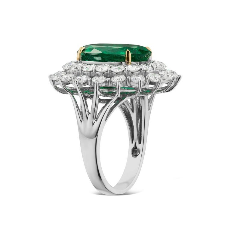 EMERALD AND DIAMOND RING BY TAKAT A rich oval emerald sits with round shaped diamonds in a substantial white gold setting.  Item:# 02418 Setting:18K W Color Weight:5.27 ct. of Emerald Diamond Weight:2.83 ct. of Diamonds