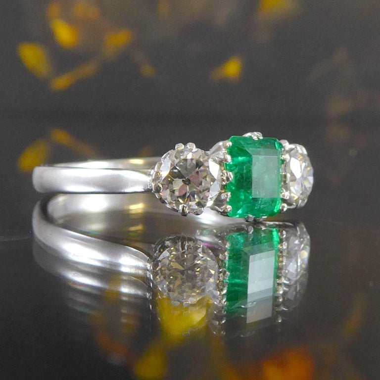 An emerald and diamond set three stone ring set with a rectangular shaped step cut emerald approx. 5.88mm x 4.66mm x 3.82mm deep and set within a double six claw basket style setting.  The emerald is flanked to each side by an early brilliant cut