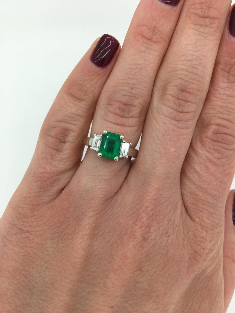 Classic three stone Emerald ring with flanking Emerald Cut Diamonds crafted in 14K white gold.   Gemstone: Emerald & Diamond Gemstone Carat Weight: Approximately 1.65CT Emerald Diamond Carat Weight:  Approximately .39CTW Diamond Cut: Emerald
