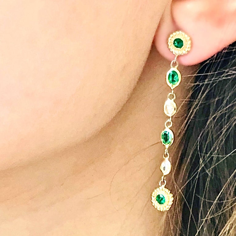 Fourteen karats yellow gold pear shape diamond and emerald braided interlacing drop earrings  Earrings are 1.75 inches long Four oval emeralds weighing 0.85 carats Four round emeralds weighing 0.60 carats Four pear shape diamond weighing 0.32 carat