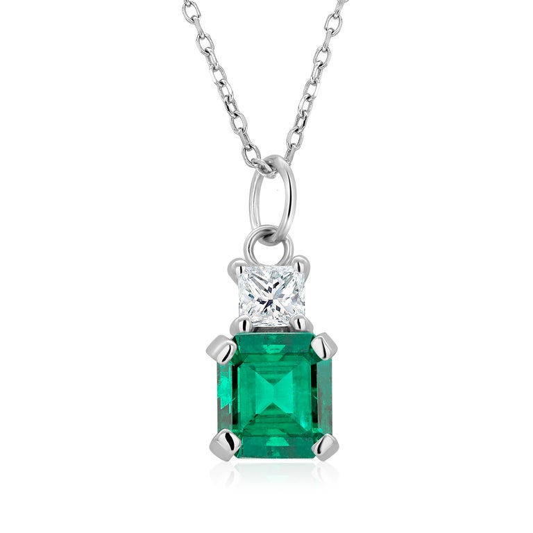14 karats white gold necklace pendant with emerald-shaped emerald Necklace measuring 16 inches long Colombia emerald-cut emerald  weighing 0.85 carats One princess cut diamond weighing 0.15 carats Emerald color hue is grass green Cable chain