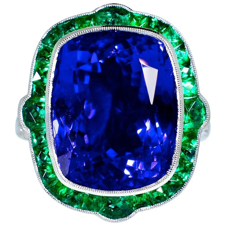 Fancy French cut natural Colombian emeralds displaying a bright green clear color surround one of the finest natural large Tanzanites we have encountered. This stone has a pure deep but exceedingly bright blue color with a slight hint of purple.