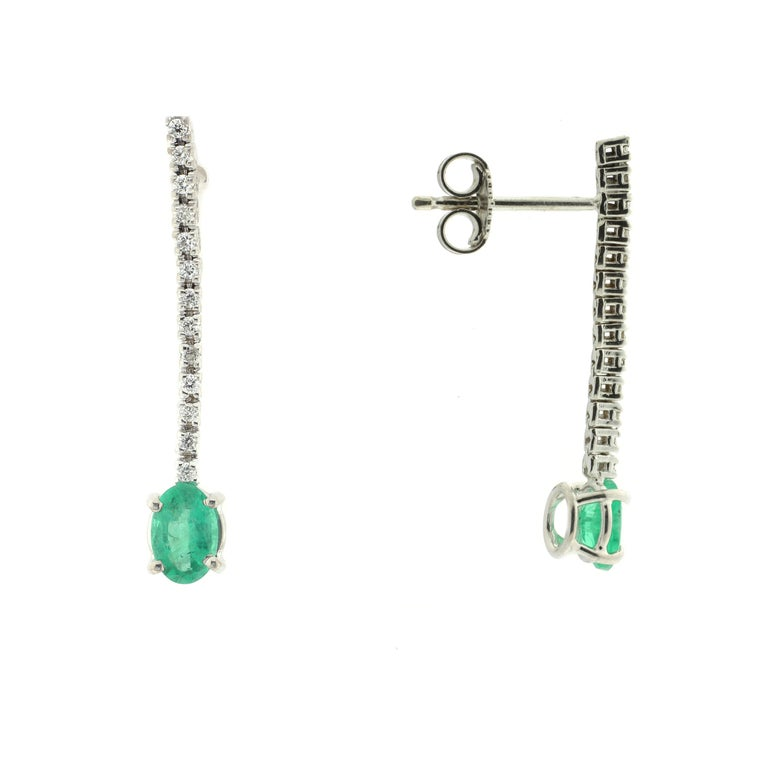 Stunning in their simplicity, these romantic drop earrings are masterfully handmade from 18-karat white gold which perfectly sets off the delicate row of white diamonds and striking solitaire emerald.   These earrings have post backs with butterfly