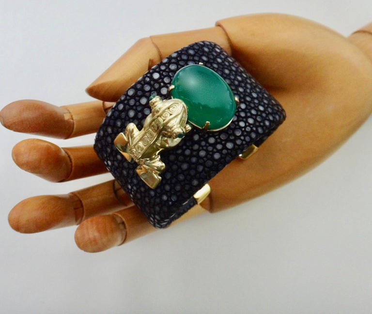 The Inca Frog Cuff is a whimsical composition of an 18k yellow gold frog finished with cabochon emerald eyes.  The frog is paired with a flawless Botswana agate of a rich emerald green color that highlights the frog's emerald eyes.  Throughout