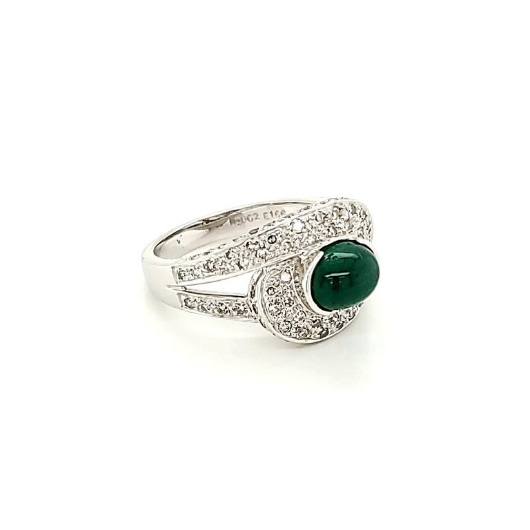 Emerald Cabochon And Diamond Ring:  A Vivid Green Cabochon Emerald weighing 1.66 carat, with embellishment of White Diamonds on the shank weighing 0.63 carat. A unique twist on a simple design coupled with the regal look of the Emerald makes the