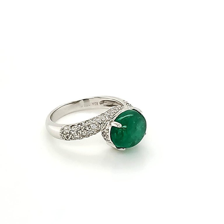 Emerald Cabochon And Diamond Ring:  A Vivid Green Cabochon Emerald weighing 2.73 carat, with embellishment of 60 White Diamonds on the shank weighing 0.48 carat. A unique twist on a simple design coupled with the regal look of the Emerald makes the