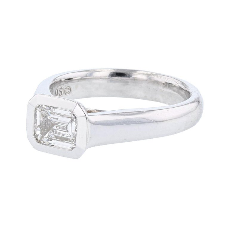 This ring is made with 14 karat white gold and features a bezel set  1.01ct  IGI certified emerald cut diamond (IGI certification number 9209818), with a color grade (E) and clarity grade (SI2).