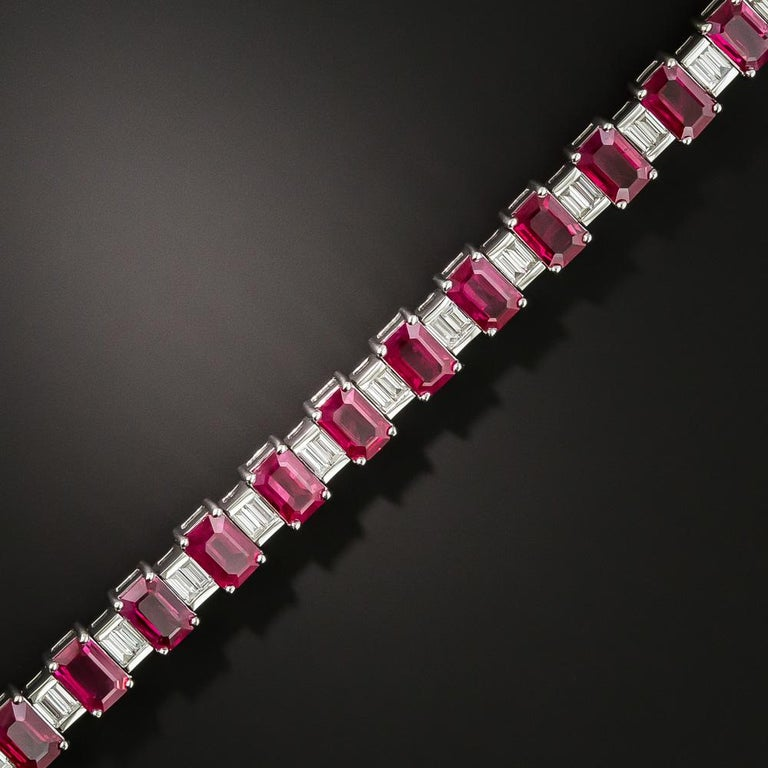 Twenty-four perfectly matched emerald-cut rubies, together weighing 14.00 carats and interspersed with seamlessly-set pairs of icy-white baguette diamonds, cast a gorgeous, glorious, electric candy apple red glow, all around this exceptional modern