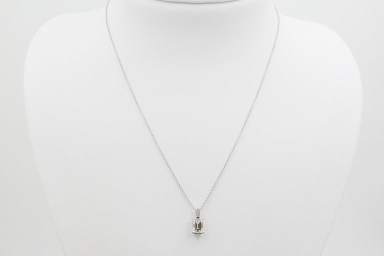 This charming 18k white gold pendant features one emerald cut diamond, with J coloring and VS2 clarity and 1.33ctw and one baguette diamond on bail, weighing .11ctw.
