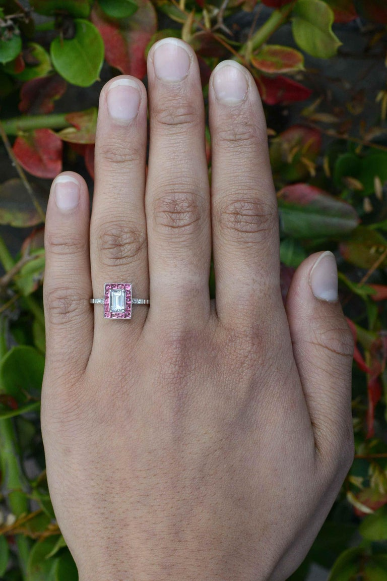 An unforgettable emerald cut diamond Art Deco style engagement ring centered by a dazzling 3/4 carat step cut with exceptional clarity and brilliance. Smartly surrounded by a halo of 14 of the cutest pink sapphire cabochons that lend an elegant