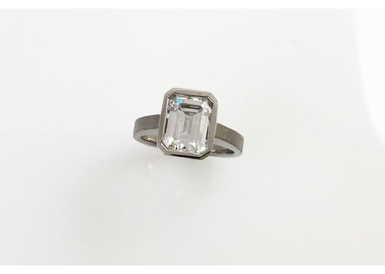 Our modern version of a classic, this Emerald Diamond Bezel Solitaire Ring is great as an engagement ring or as a right hand ring. This ring shows the stone's culet which is visible underneath the bezel and can be seen from the side. The ring is