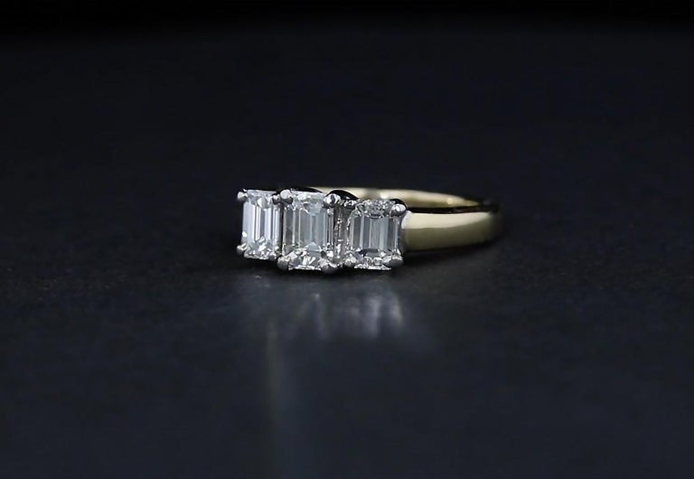 Dual toned 14k gold sets the stage for a glittering trio of emerald cut diamonds in this estate engagement ring. White gold settings bring out the natural white color of the diamonds while a yellow gold band adds contrast. The center emerald diamond