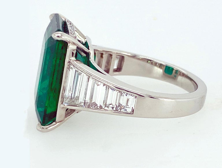 A single, emerald cut Emerald accented with six graduated emerald cut Diamonds is set in a hand fabricated,  Platinum setting. Certified  Emerald:  8.88 carats Eight Emerald cut Diamonds (5mm down to 3mm in length) and Diamond pave, 1.94 carats