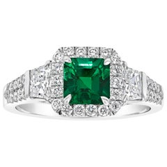 Emerald Cut Emerald and Diamond Three-Stone Halo Engagement Ring