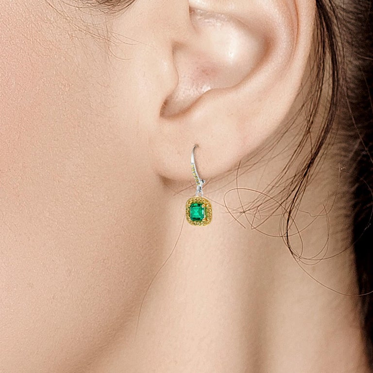 Fourteen karat white gold hoop earrings  Emerald, with yellow sapphire accents Emerald cut emerald weighing 1.85 carat  Yellow Sapphire weighing 0.40 carat  Earrings measuring 1.5-
