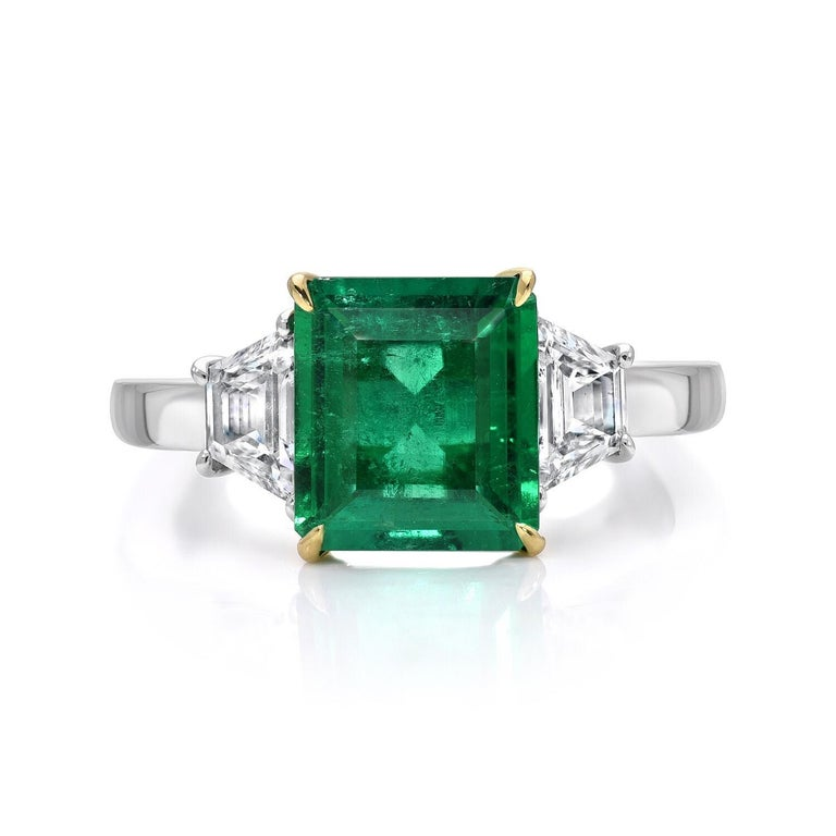 Colombian Emerald engagement ring featuring an emerald cut weighing a total of 1.85 carat flanked by a pair of Trapezoid diamonds weighing a total of 0.60 carats in Platinum. The AGL certificate is attached to the images for your convenience.  Ring