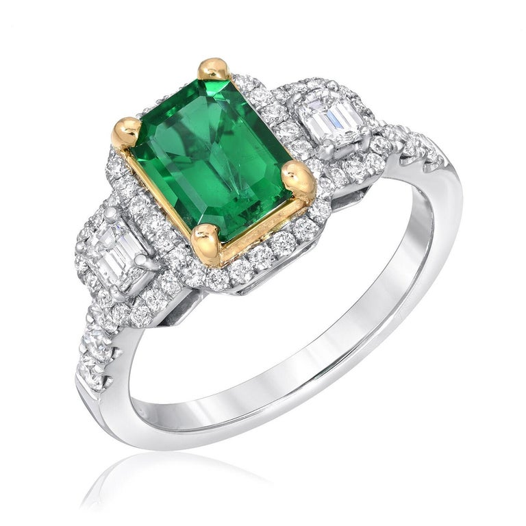 Emerald ring set with a 1.24 carat emerald cut, and a total of 0.74 carats of emerald cut diamonds and round brilliant diamonds. This three-stone Emerald ring is crafted in 18K white and yellow gold. Emerald ring size 6.5. Resizing is complimentary