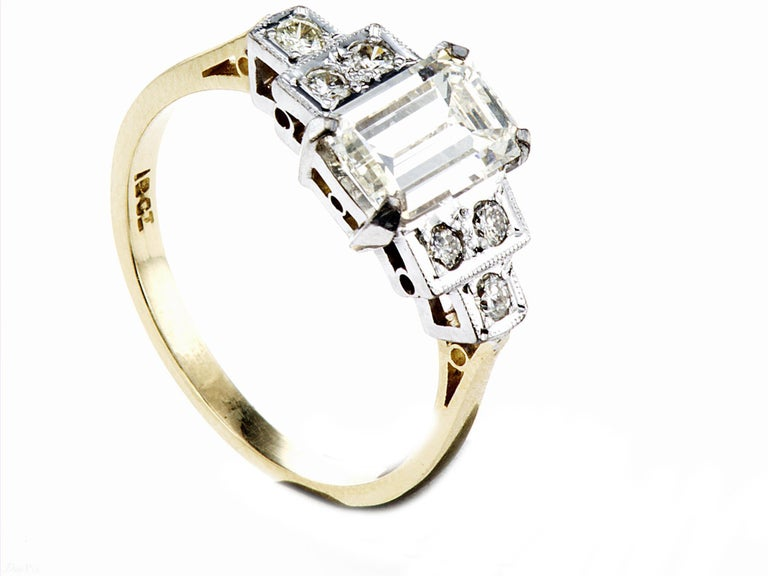 Emerald-Cut Natural Diamond Ring The central diamond measures 8.78mm x 5.64mm x 3.51mm Weighing 1.50ct. GradedI IJ VS1. The supporting shoulder stone 3 to each side weigh .12ct also I/J VS. The diamonds mounted in a platinum setting to an 18ct