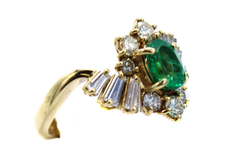 Masterfully hand-crafted in 18 karat yellow gold this abstractly designed 1970s ring features an oval brilliant cut emerald flanked by round and tapered baguette cut diamonds. The emerald has a luscious forest green color and is extremely well