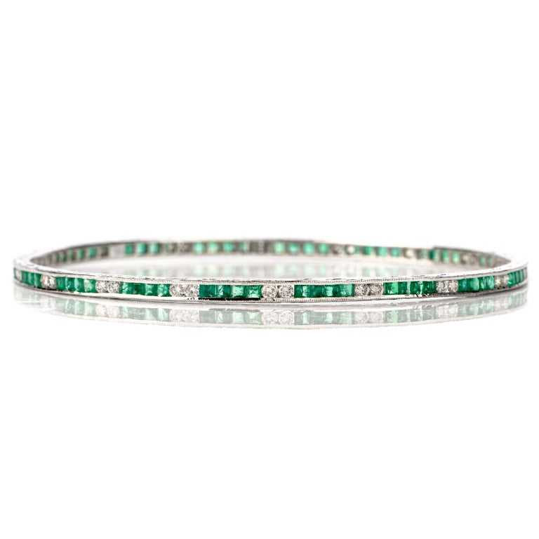 This stunning emerald and diamond bangle bracelet is crafted in 18-karat white gold. Composed of a pattern of four channel-set emerald-cut emeralds and two channel-set round brilliant diamonds. The 72 genuine emeralds collectively weigh