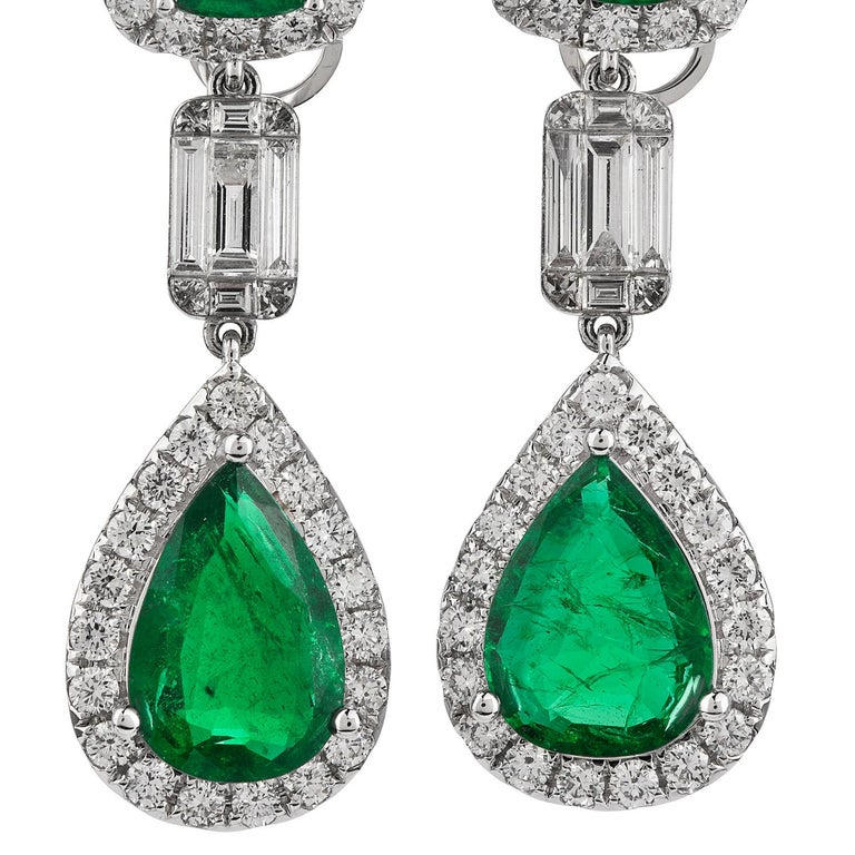 Celebrate yourself with these Diamond & Emerald Dangle drop earrings  weighing approximately 13.6 grams  Expertly crafted in solid 18K white gold, Featuring (2) Cushion cut, prong-set, and (2) Pear cut, prong-set Vibrant Emeralds weighing
