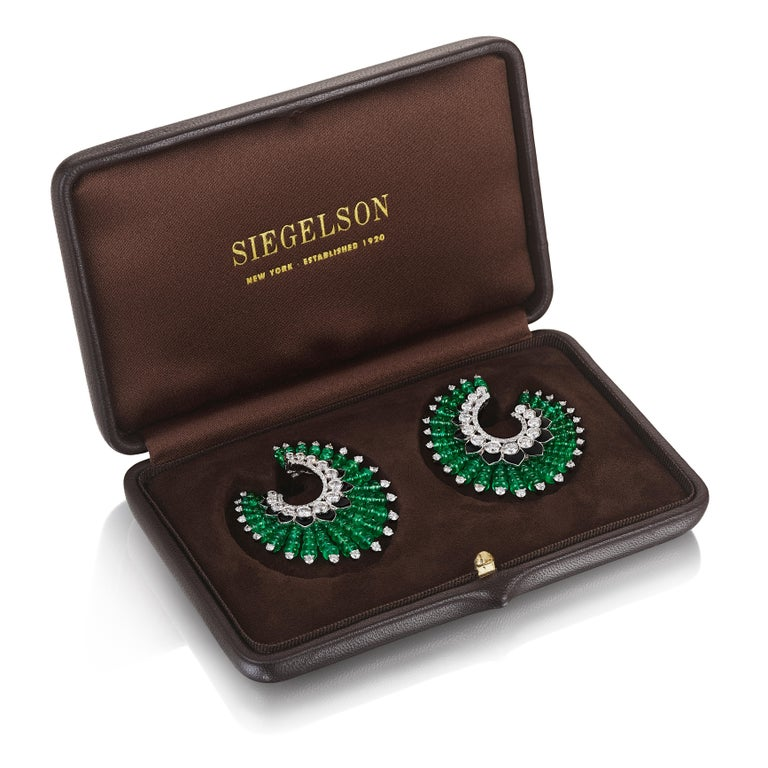 A pair of hoop earrings composed of a graduated series of emerald bead segments, with a diamond at the end, emanating from a central spiral of diamonds and black enamel petals; mounted in white gold