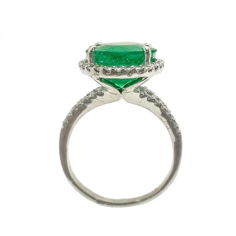 Glamorous emerald diamond ring. Handcrafted green, oval faceted natural emerald encased in open mounting with four round head prongs, accented with round brilliant cut diamond. Beautiful high polished cocktail ring set in 14 karat white gold.