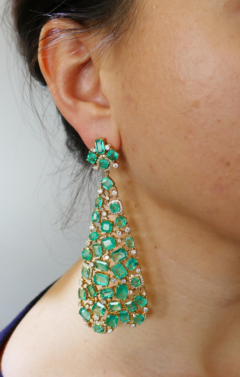 Dramatic dangle earrings. The earrings are made of 18 karat (tested) yellow gold and set with emeralds and round brilliant cut diamonds. Beautiful color combination of vivid green emeralds and sunshine of yellow gold with a subtle sparkle of