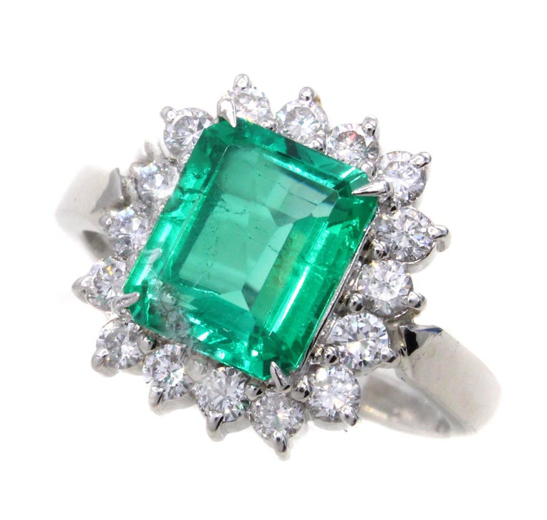 A beautifully laid out vivid green natural emerald weighing 1.99 carats is the center-piece of this impressive ring. The emerald is very clean and has very few natural inclusions. Well cut with perfect proportions this emerald shows a much larger