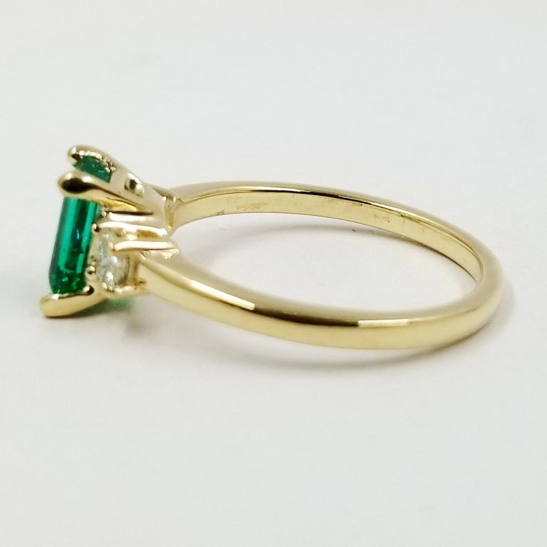 New 14 karat yellow gold ring featuring one 0.85 carat Emerald cut emerald and 2 Princess cut diamonds totaling 0.20 carat of VS clarity & G color. Current finger size is 7.5; purchase includes one free sizing.