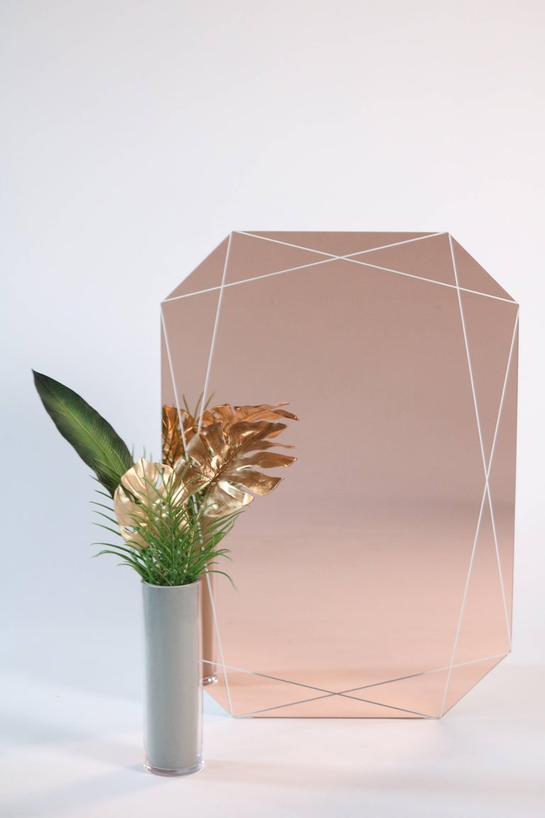 These emerald shaped mirrors convey faceted geometry through delicately etched line work shining through peach, smoke and crystal clear surfaces. Available in peach, smoke or low iron clear 1/4