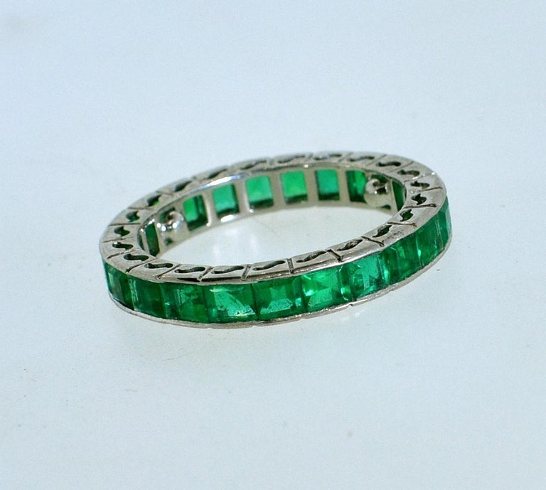 Emerald eternity band in 18K white gold with 23 fine bright, well matched and well cut, natural Colombian emeralds of very fine quality and amounting to approximately 3.4 cts.  Now a size 6 and can be sized. This band now has