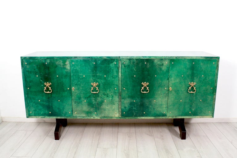 Unique lacquered emerald green goatskin credenza, high quality brass details. Designed by Aldo Tura in the 1960s. Two glass shelves (on each side) inside on a wooden mahogany base.